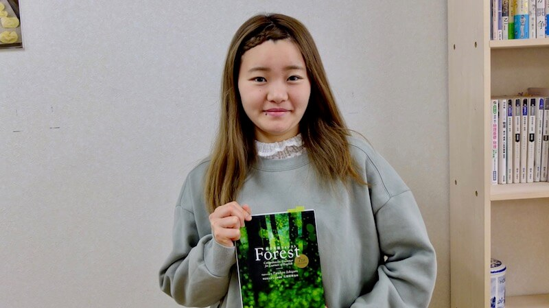 英語の参考書を持っている女子高校生