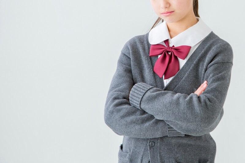 腕を組んで考える女子高校生